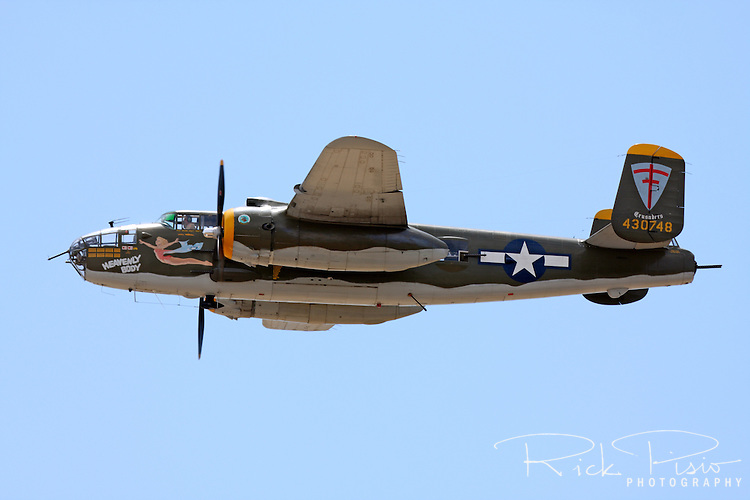 """A North American B-25 Mitchell in flight during the 2009 Madera Air Show in Madera, California. Serial #44-30748 was first delivered to the USAAF in 1944 and later flew as a sprayer in Wyoming before landing the role of """"M&M"""" and """"Miss Renee"""" in the movie version of the Joseph Heller novel 'Catch 22.' The Mitchell is well known as the aircraft used during the Doolitlle Raid of Tokyo in the first years of World War II."""