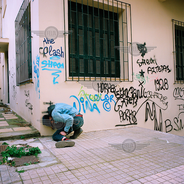 A drug addict crouches, doubled-up against a wall on Stefri Hill in the Exarchia neighbourhood of central Athens. Due to the low police presence, and the opening of a new drop-in centre for addicts, many users stay around Exarchia to buy and use drugs.