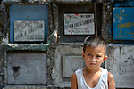"A boy in the Manila North Cemetery. Hundreds of poor families live here, dwelling in and between the tombs and mausoleums of the city's wealthy. They are often discriminated against, and many of their children don't go to school because they're too hungry to study and they're often called ""vampires"" by their classmates. With support from United Methodist Women, KKFI provides classroom education and meals to kids from the cemetery at a nearby United Methodist Church."