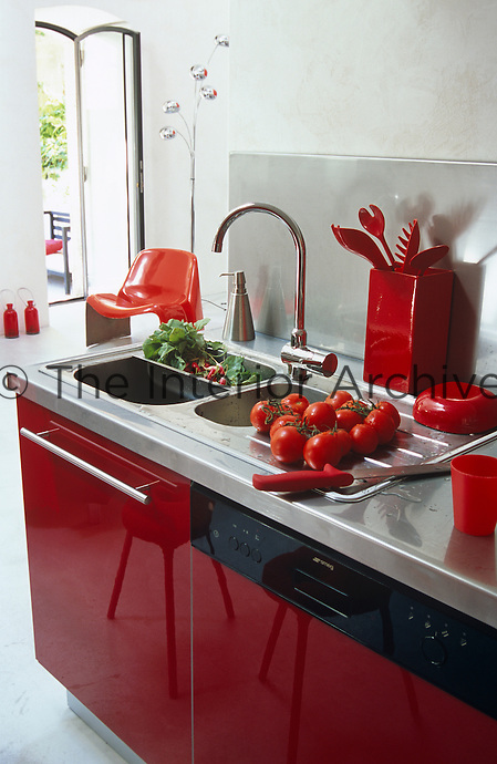 Tomatoes and radishes have been washed in the stainless steel sink of this gleaming red kitchen