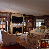 In the drawing room the central flatscreen TV is incorporated into the mantelpiece with three sofas grouped around a coffee table