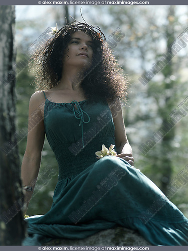 Beautiful woman wearing a wreath made of tree branches and a long green dress sitting alone in the nature with a dreamy serene look on her face