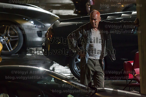 US actor Bruce Willis rests on set during a shooting of his next movie fifth in the Die Hard series titled Good Day to Die Hard in Budapest, Hungary on July 11, 2012. ATTILA VOLGYI
