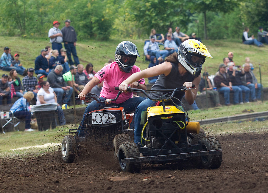 """The Powder Puff lawnmower race takes place with  Lindsey Davis (L) and Courtney Nicholson (R) at the annual """"Territorial Days"""" festival in Amboy Sunday July 10, 2016. Other events during the celebration included a logging show, musical performances, an art show and a carnival. The celebration highlights the area's connection to logging and pioneering.  (L to R) Lindsey Davis, Courtney Nicholson, Skylar Riggs, and Emily Hoffman. (Photo by Natalie Behring/ for the The Columbian)"""