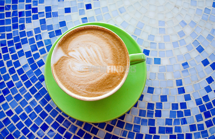 Ornate Latte in Green Coffee Mug on Blue Mosaic Tabletop