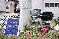 A campaign sign and audio equipment is seen next to a grill after Democratic presidential candidate and spiritual guru Marianne Williamson spoke to a small crowd in the back yard of Kathleen O'Donnell at a campaign house party event in Keene, New Hampshire, on Wed., May 22, 2019.