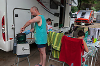 Switzerland. Canton Ticino. Tenero. Camping Campofelice. A motorhome (C) and a caravan (R) belonging to a german family. The father is cooking the supper on a gas stove while his son plays around and his daughter reads a book seated at the table. A campervan (or camper van), sometimes referred to as a camper, or a caravanette, is a self-propelled vehicle that provides both transport and sleeping accommodation. A motorhome (or motor coach is a type of self-propelled recreational vehicle (RV) which offers living accommodation combined with a vehicle engine. Motorhomes are part of the much larger associated group of mobile homes which includes caravans, also known as tourers, and static caravans. A caravan, travel trailer, camper or camper trailer is towed behind a road vehicle to provide a place to sleep which is more comfortable and protected than a tent. It provides the means for people to have their own home on a journey or a vacation. Campers are restricted to designated sites for which fees are payable. 19.07.2018 © 2018 Didier Ruef
