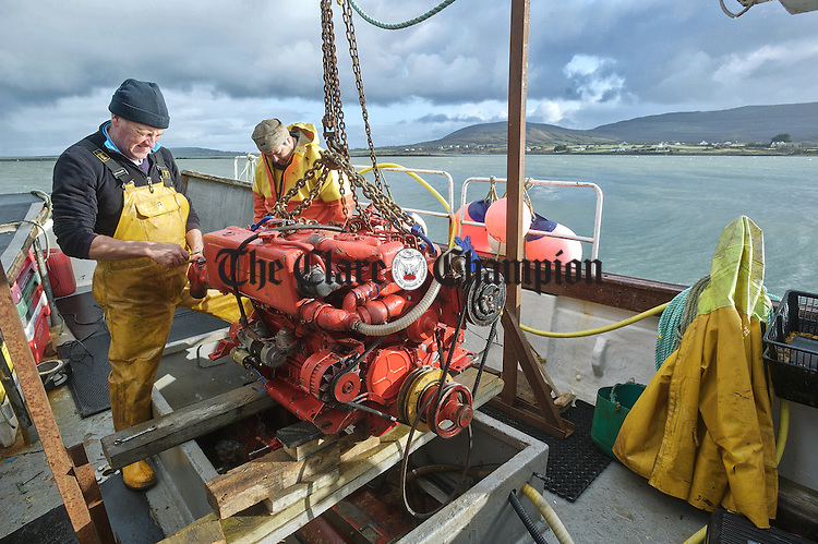 Patsy Mullins and Jason Quinlivan busy re-engining their fishing boat at the New Pier in Ballyvaughan ahead of the forthcoming season. Photograph by John Kelly.