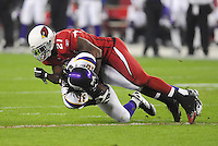 Dec 6, 2009; Glendale, AZ, USA; Minnesota Vikings wide receiver (18) Sidney Rice is tackled by Arizona Cardinals safety (21) Antrel Rolle at University of Phoenix Stadium. The Cardinals defeated the Vikings 30-17. Mandatory Credit: Mark J. Rebilas-