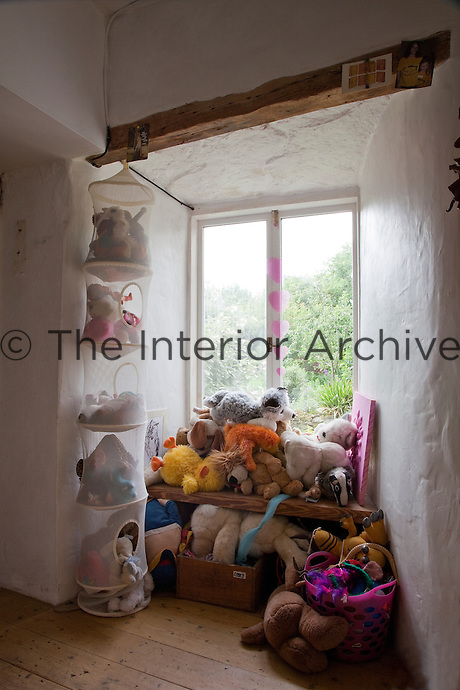 A mountain of soft toys is stored in the window alcove of a child's bedroom