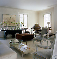 The contemporary living room is furnished with a large globe, grey velvet armchairs and an oversized ottoman
