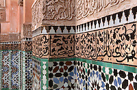 Carved stucco decoration and zellige tiles from courtyard of Ben Youssef Madrasa, Medina, Marrakech, Morocco. The stucco is carved in an Iraqi kufic style of calligraphy interwoven with vegetal designs. Below is zellige tilework, terracotta tiles covered with 5 colours of enamel and set into plaster, typical of the Hispano-Moresque period. The Madrasa is an Islamic theological college founded in the 14th century and rebuilt by the Saadians in the 1560s. It is named after the Almoravid Sultan Ali ibn Yusuf, who reigned 1106-42. Picture by Manuel Cohen
