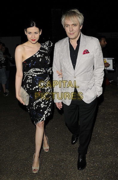 Nefer Suvio &amp; Nick Rhodes<br /> The Serpentine Gallery Summer Party, Serpentine Gallery, Kensington Gardens, Hyde Park, London, England.<br /> June 26th, 2013<br /> full length grey gray suit black dress one shoulder sleeve print trousers couple <br /> CAP/CAN<br /> &copy;Can Nguyen/Capital Pictures