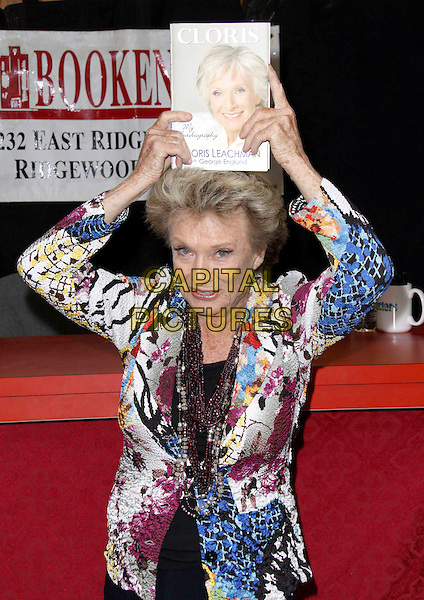 "CLORIS LEACHMAN.Nine-time Emmy Award Winner and Star of Dancing with the Stars signs her new book ""Cloris"" held at Bookends Book Store, Ridgewood, New Jersey, USA,.1st April 2009..half length black white blue multi-coloured print jacket beads necklace book holding up above on head funny .CAP/ADM/PZ.©Paul Zimmerman/Admedia/Capital Pictures"