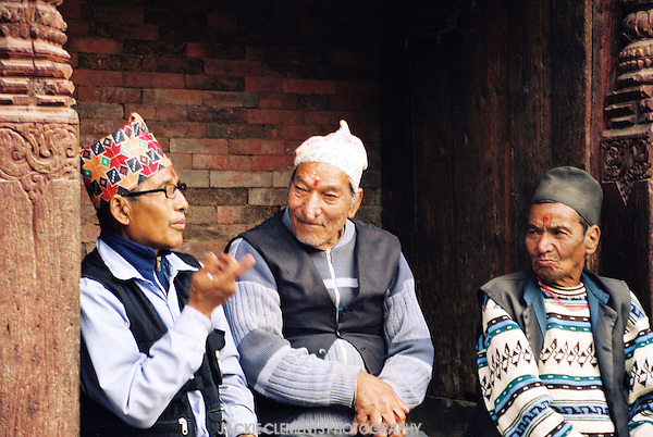 Three men in traditional Nepalese hats, or topis, sit together in a beautifully carved doorway.