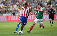 Paulo Da Silva (14) tries to turn against Andres Guardado (18). Mexico defeated Paraguay 3-1 at the Oakland Coliseum in Oakland, California on March 26th, 2011.