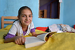 Sarah Ismili, an 11-year old Roma girl in Suto Orizari, the Macedonian municipality that is Europe's largest Roma settlement, reads her school homework in her family's home.