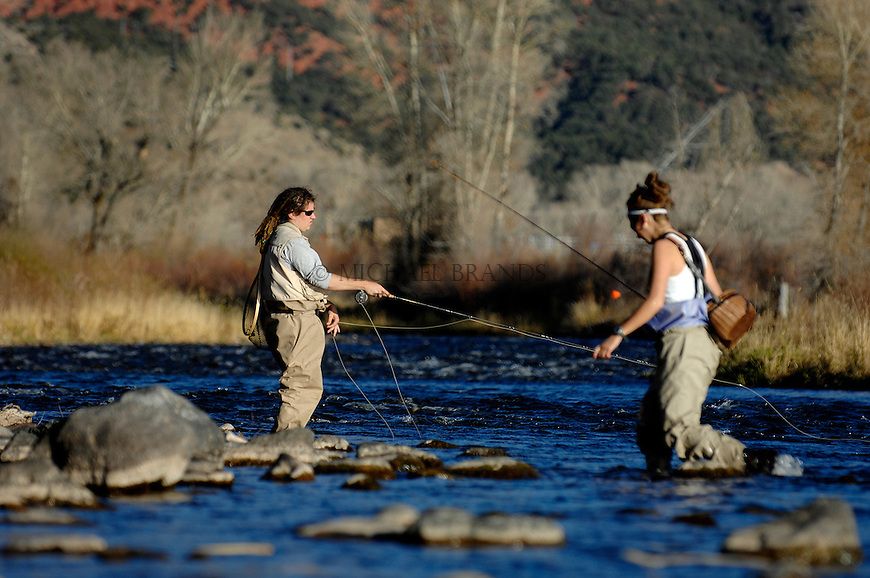 """Tory Amorello, of Carbondale, right, heads for shore as Dan Berg of Basalt fishes on the Roarding Fork River downstream from Basalt on Sunday. """"It's a beautiful day!"""" says Berg. © Michael Brands."""