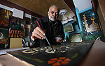 Hashem Kalloub, 59, a Palestinian artist, works at his workshop in Gaza city on December 26, 2018. Kalloub has drawing and calligraphy talent, take it as a work since 38 years to support his family. Photo by Mahmoud Ajjour