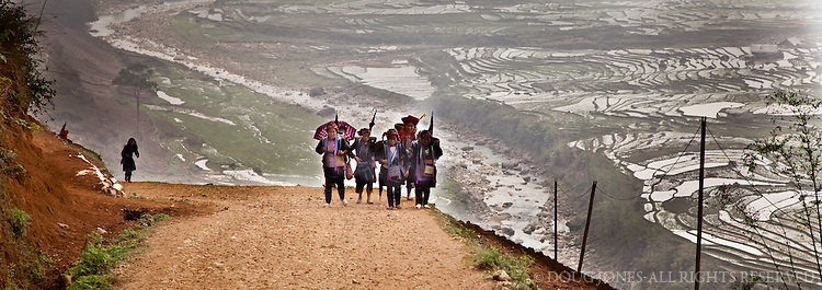 Black Hmong and Red Dzao women outside of Sapa make their way to a hillside village outside of Sapa.