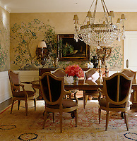 The elegant dining room has hand-painted wallpaper and a rosewood dining table with a large chandelier hanging above it