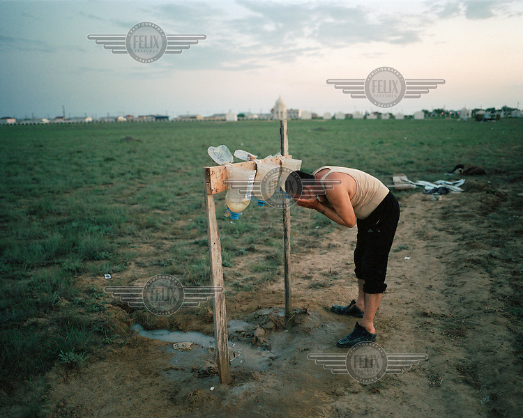 Abish cleans his face at the end of the day after working long hours at a cemetery near the Caspian Sea coast. He uses a temporary washing station created from upturned water bottles, with screw caps used like taps. .
