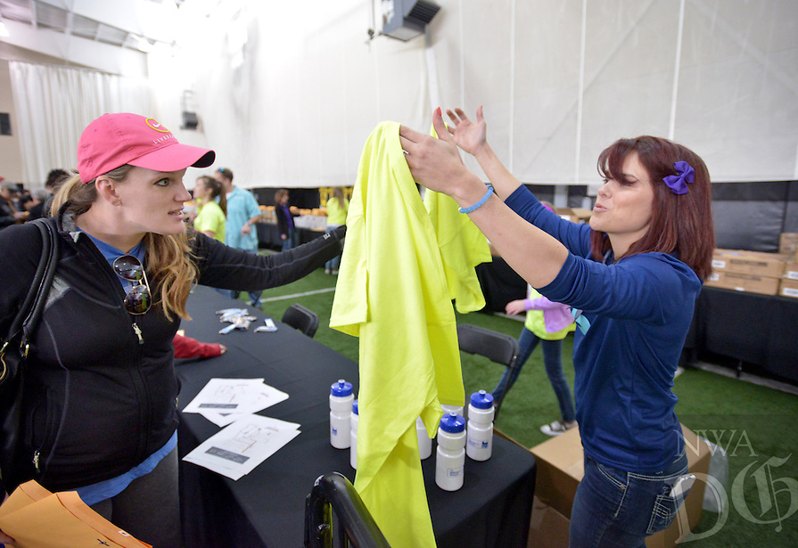 NWA Democrat-Gazette/BEN GOFF -- 03/27/15 Emily Deal, an employee with the Bentonville Parks & Recreation Department, checks in Tiffany Whitley of Rogers, who will be participating in the fun run with daughter Halle Whitley, during the RunBentonville Half Marathon Runners Health & Wellness Expo & Packet Pick Up in the in the Tiger Athletic Complex Multi-Purpose Facility at Bentonville High School on Friday Mar. 27, 2015.