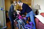Olga Batiounina and William Massart steady their daughter Sandra Massart, 10, in her wheelchair at the family's apartment in Durham, NC, USA, on Wednesday, February 15, 2012.  Sandra Massart is being treated at Duke University Hospital in Durham, NC, for MLD, a degenerative condition.  Photo by Ted Richardson