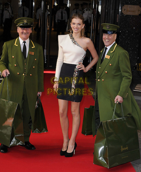 Lily Donaldson.opens the Harrods Summer 2012 Sale, Harrods, Knightsbridge,  London, England..16th June 2012.full length black white one shoulder sleeve embellished jewel encrusted dress skirt top hand on hip uniform green bags shopping .CAP/CAN.©Can Nguyen/Capital Pictures.