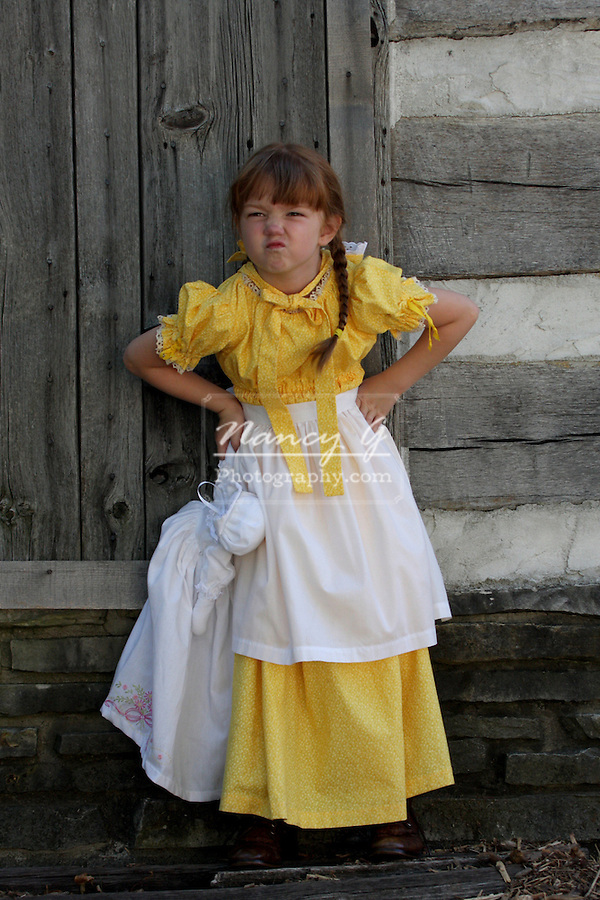 A young girl dressed in a prairie dress with a sassy face