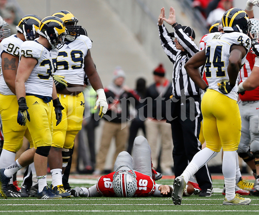 Ohio State Buckeyes quarterback J.T. Barrett (16) lays on the ground with a broken right ankle after being tackled by a Michigan defender during the fourth quarter of the NCAA football game at Ohio Stadium on Nov. 29, 2014. Barrett did not return to the game. (Adam Cairns / The Columbus Dispatch)