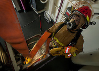 120106-N-DR144-297 INDIAN OCEAN (Jan. 6, 2012) Damage Controlman Fireman Cameron Michalak, a member of the ship's flying squad guides a hose down a ladder well as a hose team prepares to combat a simulated fire several decks below during a drill aboard the Nimitz-class aircraft carrier USS Carl Vinson (CVN 70). Carl Vinson and Carrier Air Wing (CVW) 17 are underway on a Western Pacific Deployment.  (U.S. Navy photo by Mass Communication Specialist 2nd Class James R. Evans/Released).