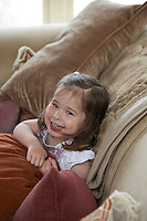 Monica Vinader's little girl happliy playing on a sofa designed by her mother