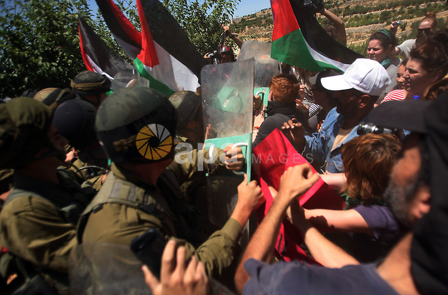 Israeli soldiers prevent Palestinians, left-wing Israeli and foreign peace activists from heading towards the Jewish settlement of Karim Tsor to protest against the confiscation of Palestinian land from the West Bank village of Beit Omar, north of Hebron, on June 2, 2012. Photo by Mamoun Wazwaz