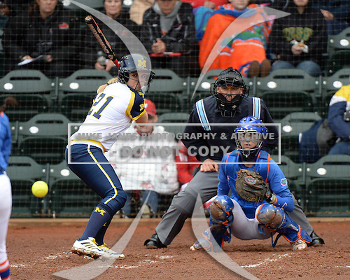Michigan Wolverines outfielder Kelly Christner (21) at bat in front of catcher Aubree Munro (1) and umpire Tyrone Miller during the teams season opener against the Florida Gators on February 8, 2014 at the USF Softball Stadium in Tampa, Florida.  Florida defeated Michigan 9-4 in extra innings.  (Mike Janes/Four Seam Images via AP Images)