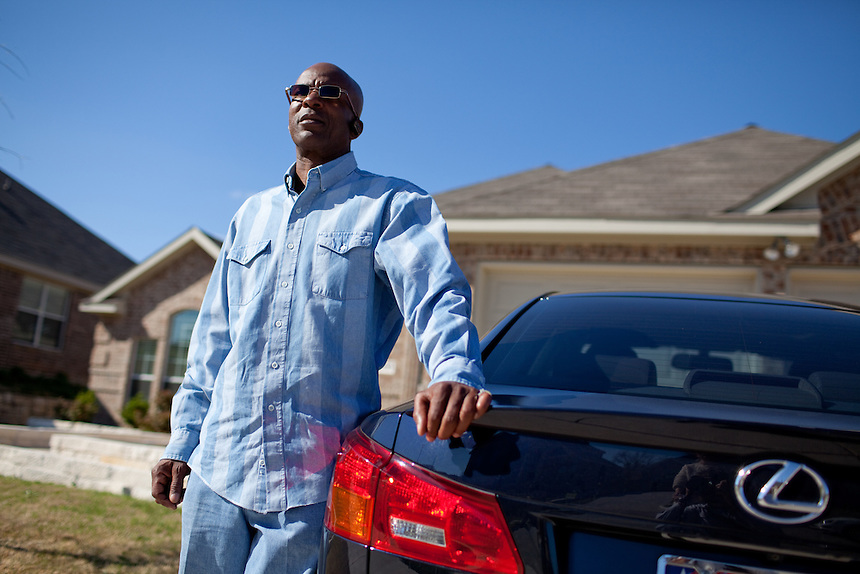 DNA Exonerated prisoner Thomas McGowan, stands next to his Lexus luxury car at his home in Garland, Texas.