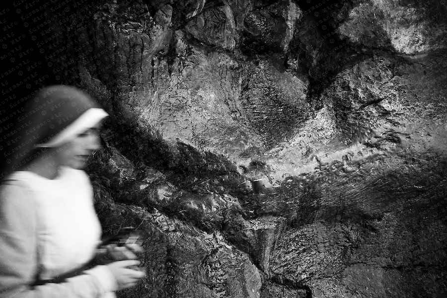 "Pilgrims pass their hands over the stone of the grotto, hoping for a miracle or a blessing by the ""Virgin of Lourdes"". 1987."