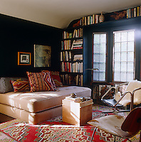 A guest bedroom has been transformed into a library with a customised bookshelf built around the windows