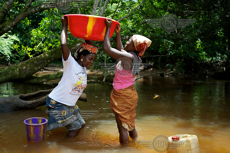 Women gather water from a muddy lake in the village of Nyonken. /Felix Features