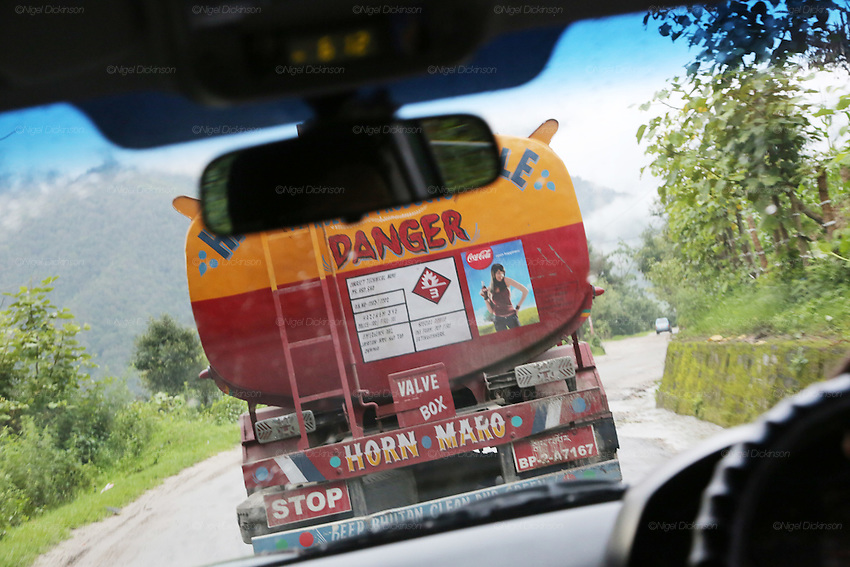 """Please blow your horn"", written on every truck and large vehicle, across the Himalayas and India, lessens the chance of acciudents..Bhutan the country that prides itself on the development of 'Gross National Happiness' rather than GNP. This attitude pervades education, government, proclamations by royalty and politicians alike, and in the daily life of Bhutanese people. Strong adherence and respect for a royal family and Buddhism, mean the people generally follow what they are told and taught. There are of course contradictions between the modern and tradional world more often seen in urban rather than rural contexts. Phallic images of huge penises adorn the traditional homes, surrounded by animal spirits; Gross National Penis. Slow development, and fending off the modern world, television only introduced ten years ago, the lack of intrusive tourism, as tourists need to pay a daily minimum entry of $250, ecotourism for the rich, leaves a relatively unworldly populace, but with very high literacy, good health service and payments to peasants to not kill wild animals, or misuse forest, enables sustainable development and protects the country's natural heritage. Whilst various hydro-electric schemes, cash crops including apples, pull in import revenue, and Bhutan is helped with aid from the international community. Its population is only a meagre 700,000. Indian and Nepalese workers carry out the menial road and construction work."