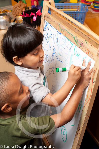 Education Preschool Headstart 3 year olds two boys playing at dry erase board one boy tracing the other's fingers with marker