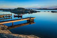 Båtfärd på spegelblankt vatten bland låga skär i ytterskärgården på Ut-Fredel iStockholms skärgård. / Outer Stockholms archipelago Sweden.