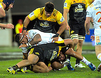 Chris Eves (top) and Leni Apisai tackle Hika Elliott during the Super Rugby semifinal match between the Hurricanes and Chiefs at Westpac Stadium, Wellington, New Zealand on Saturday, 30 July 2016. Photo: Dave Lintott / lintottphoto.co.nz