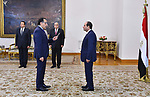 A handout picture released by the Egyptian Presidency on June 14, 2018 shows newly-appointed Prime Minister Mostafa Madbouli (L) taking the oath before President Abdel Fattah al-Sisi (R) during his swearing-in ceremony at the presidential palace in the capital Cairo. Photo by Egyptian President Office