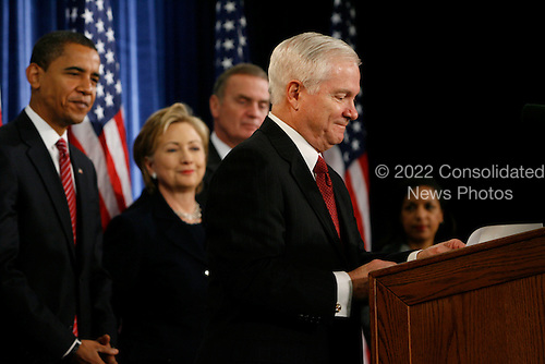 Chicago, IL - December 1, 2008 -- United States Secretary of Defense Robert Gates, at podium, speaks at a press conference for  President-elect Barack Obama, left, to announce United States Senator Hillary Rodham Clinton (Democrat of New York), nominee for Secretary of State, retired Marine General James L. Jones as national security adviser, middle right, and  Susan Rice, far right, as United Nations ambassador at the Chicago Hilton & Towers in Chicago, Illinois. Obama announced that Gates would keep his current post..Credit: Anne Ryan - Pool via CNP
