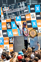 American Brett Simpson hoisting the $100,00.00 and check and trophy in victory during the final day of the 2010 US Open of Surfing in Huntington Beach, California on August 8, 2010.