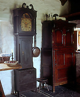 A grandfather clock and simple dresser stand side by side against one wall of the small living area