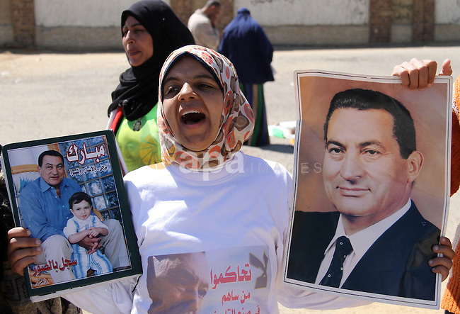 Supporters of former Egyptian president Hosni Mubarak hold his poster outside the police academy in Cairo, Egypt, on Feb. 19, 2014. Photo by Mohammed Bendari