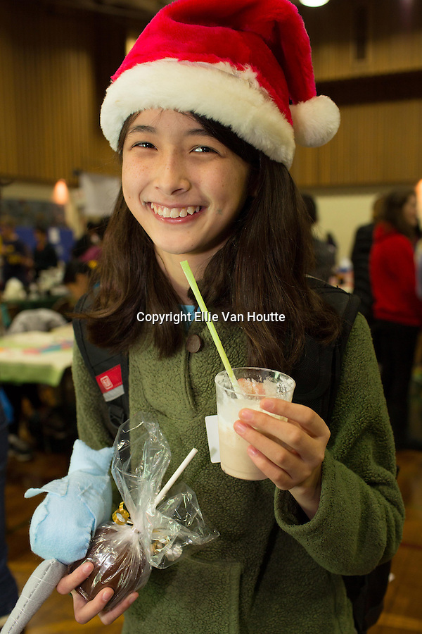 Overloaded with holiday faire goodies including a chocolate-covered apple and a chocolate milk shake, Sachi Ottoes smiles as she walks through thte faire.