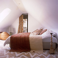 A white attic bedroom with a painted wooden floor. The room is simply furnished with a double bed with a terracotta patterned cover and a lamp. A curtained doorway leads through to an ensuite bathroom beyond.